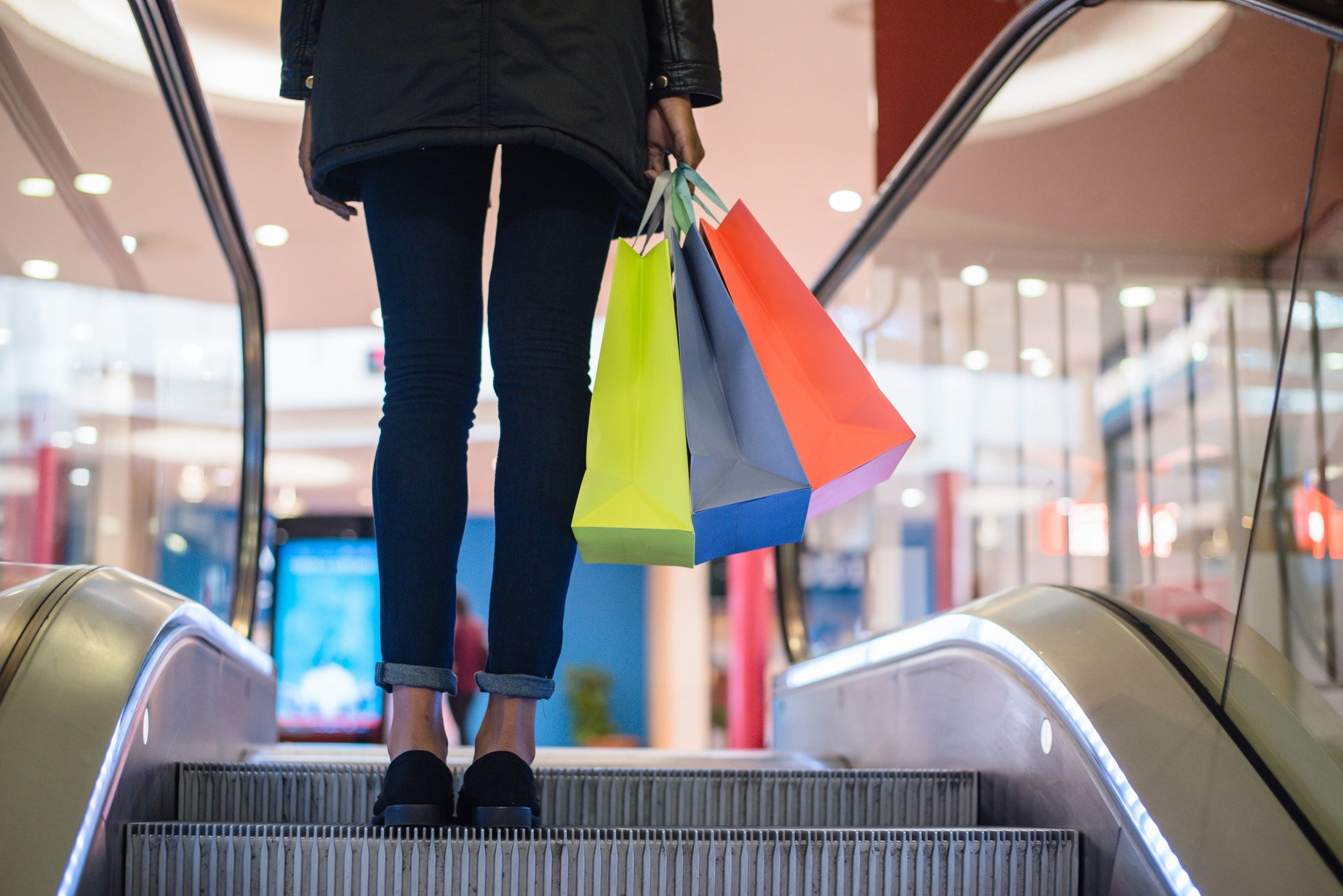 Woman legs with colourful shopping bags on the escalator in a shopping mall